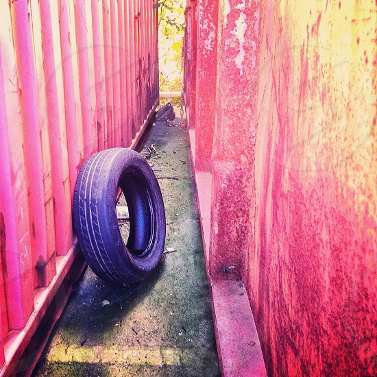black tire leaning red container photo