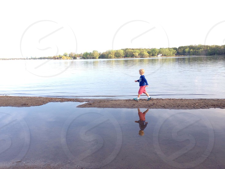 Woman in blue sleeved shirt walking on gray sand photo