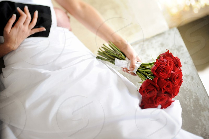 The hands of a bride hold her groom and her bouquet of bright red roses. photo