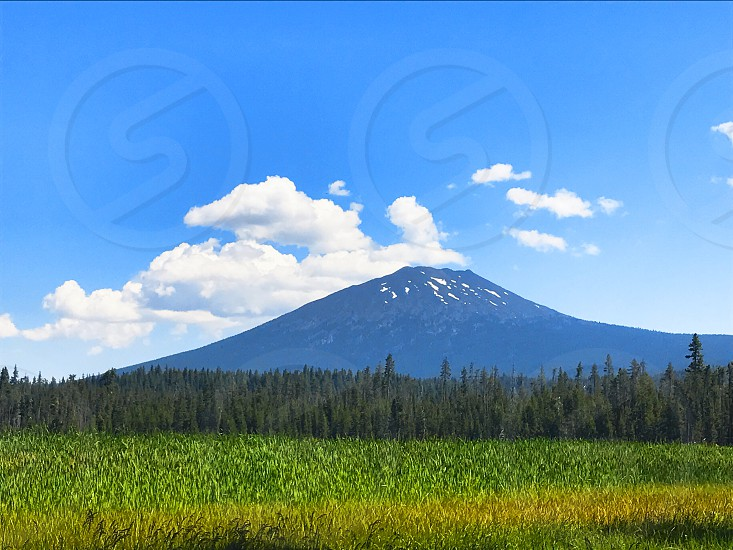 Simple minimal landscape with mountain agianst  cloudy sky photo