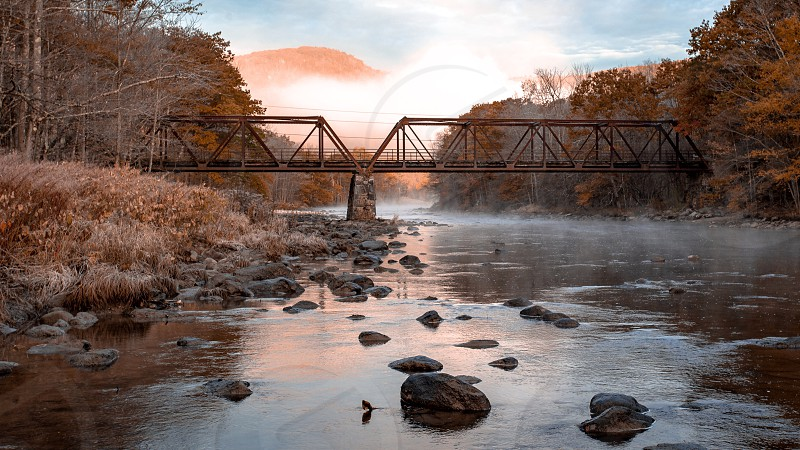 A old iron and wood bridge stretching across the river  photo