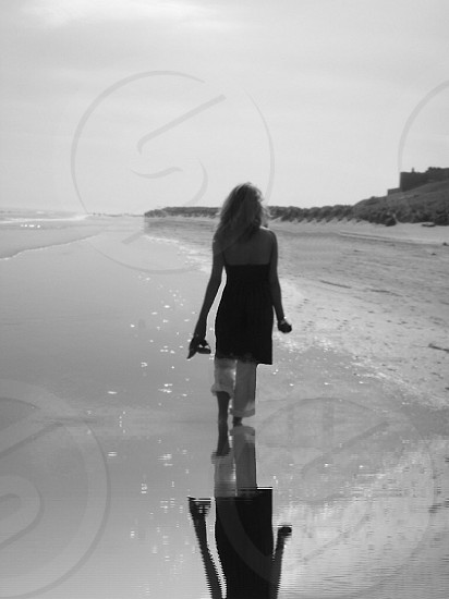 Reflectionblack and whitebarefootonthesandseashorebeach photo