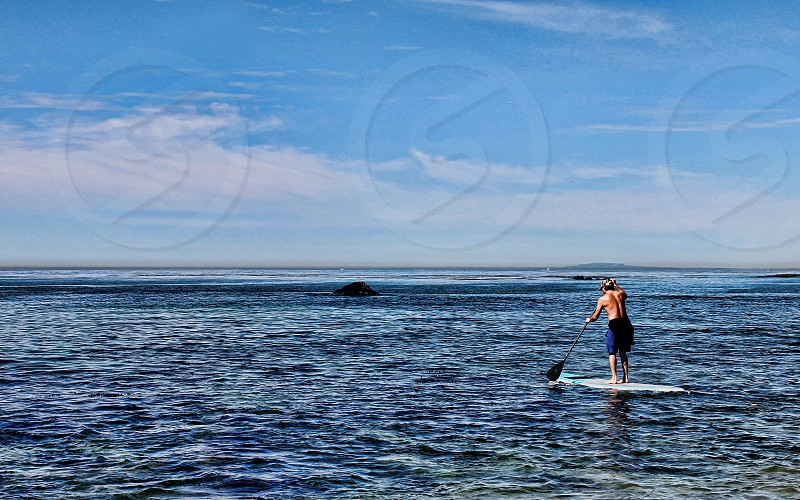 Paddle boarder on a calm blue ocean photo