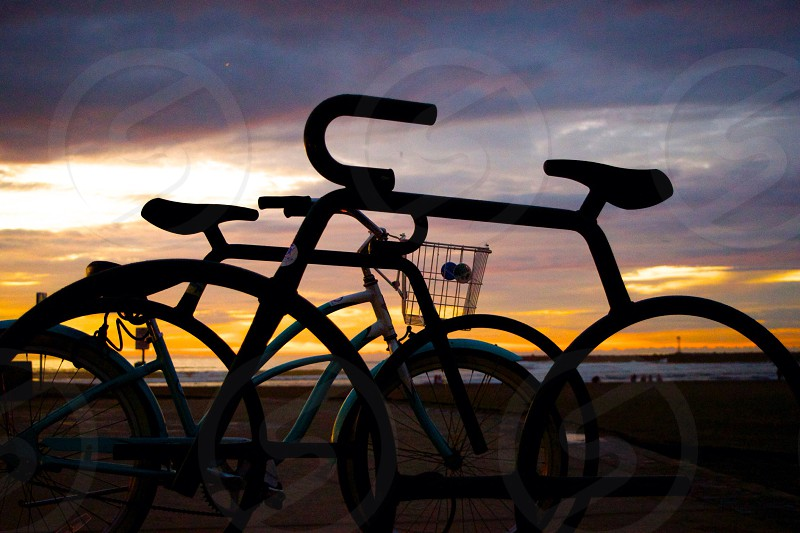 Bicycle rack at beach with teal cruiser bike with basket sunset in background beach coast life  photo