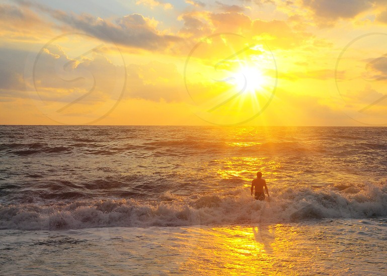 man in sea golden hour photography photo
