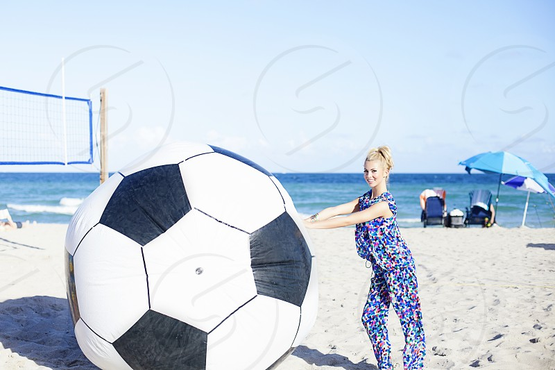 woman pushing life size soccer ball at the beach photo