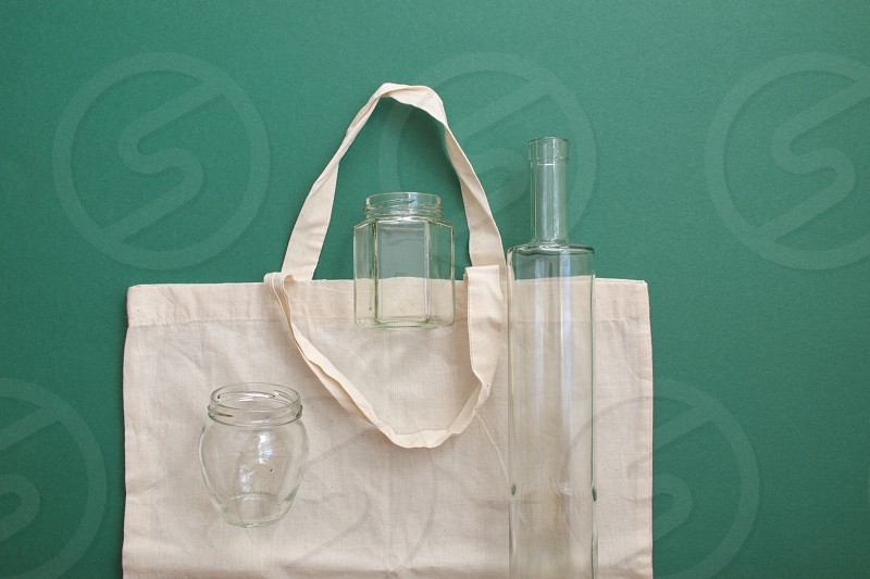 Reusable shopping bag and reusable glass bottles against the green background photo