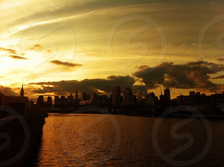 city buildings across water on sunrise photo