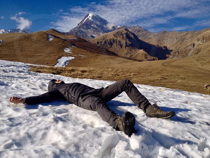 Winter mountains trip adventure vacation Georgia Kazbek man on snow tourist snow at the top having fun photo