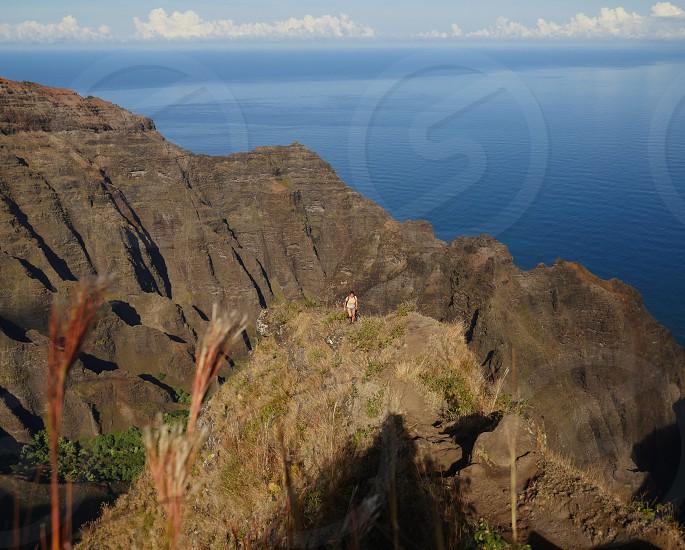 Hiker walking on sharp ridge on top of the mountain Kauai hawaii  trail photo