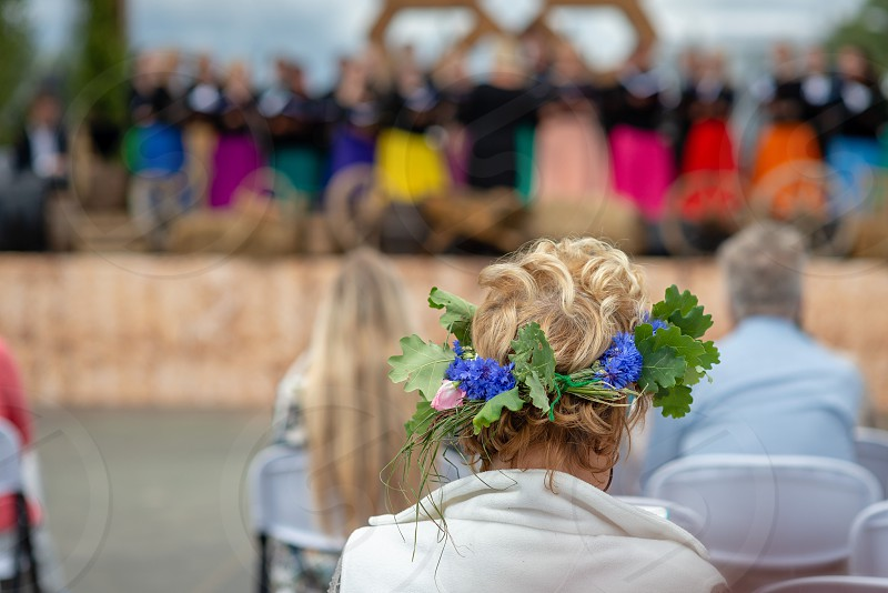 A woman with a flower crown in her head is watching a concert. View from the back. photo