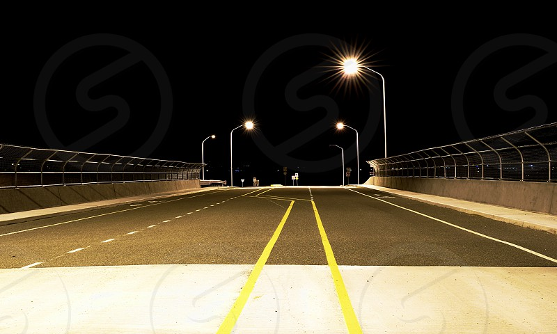 Looking down the centerline of an empty highway overpass late at night. photo