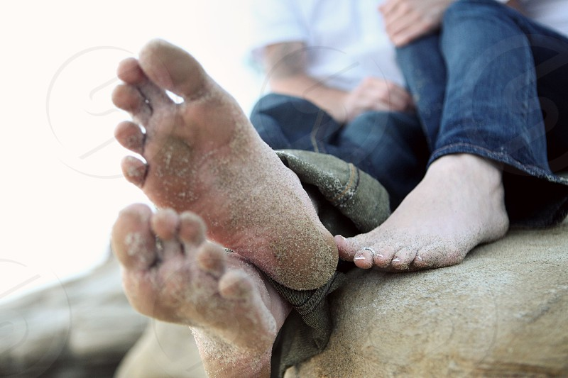 A young couple wearing jeans sit on a rock on the beach while playing with each others' feet which are covered in sand.  photo