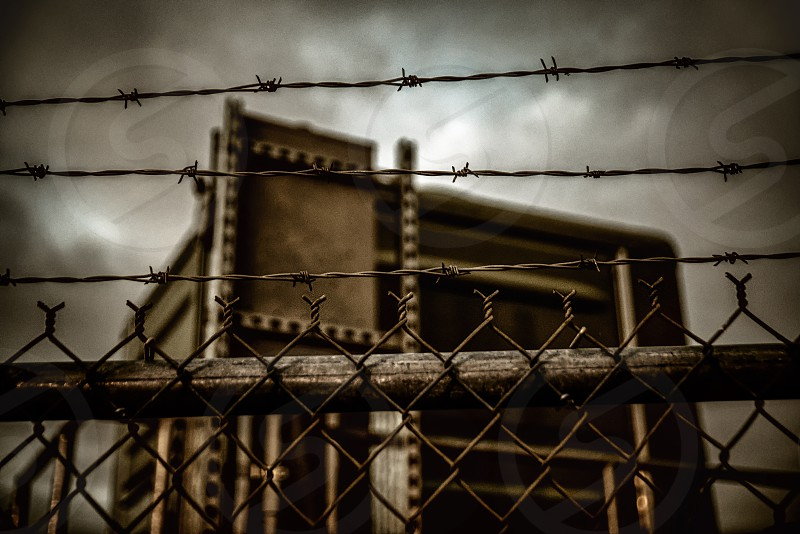 An ominous-looking building protected by a fence and barbed wire. photo