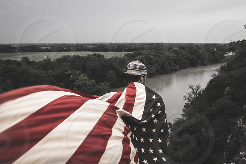 man wearing usa flag looking out at river photo