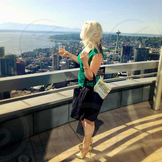 woman in gold heels black tote bag black skirt green silk top with blonde hair and wine glass overlooking city view photo