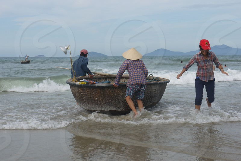 fisherman and women with bamboo boats at beach Hoi An Vietnam photo