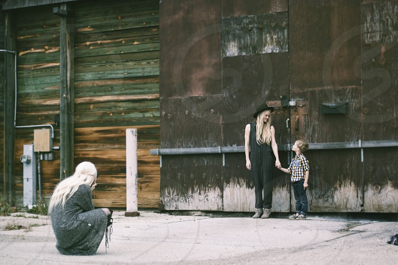 woman wearing black hat and suit standing beside child while person taking a picture photo