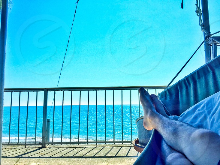 person laying on hammock near ocean during daytime photo