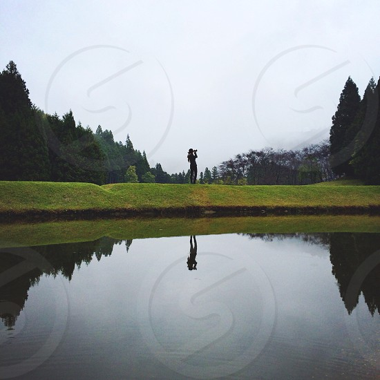 person standing on green grass field across body of water photo