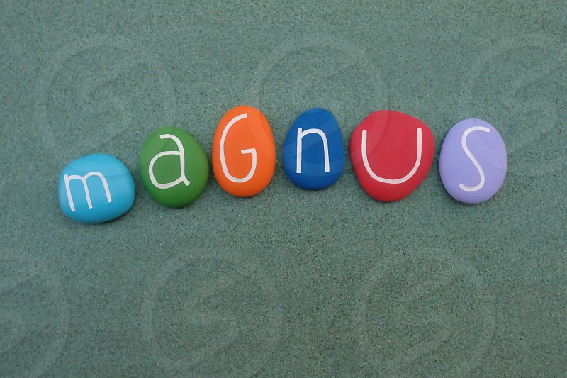 Magnus masculine name composed with multi colored stones over green sand photo
