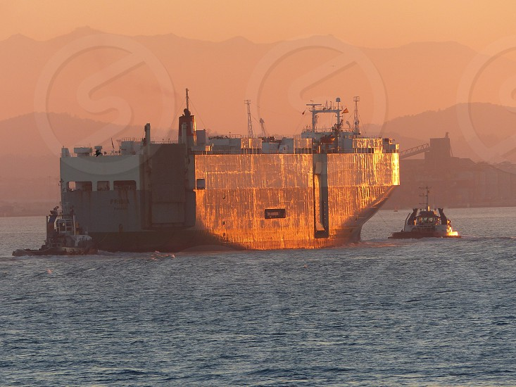 Tow boat aiding large carrier photo