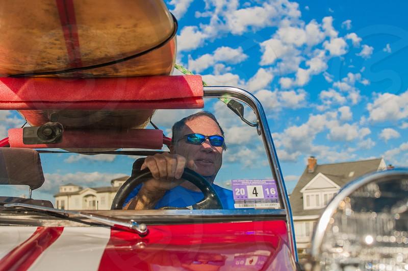 man in blue shirt riding in red and white convertible car during daytime photo