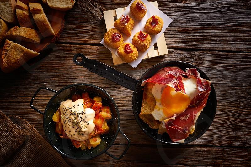 Tapas of Spain broken eggs Croquettes and Bravas potatoes photo