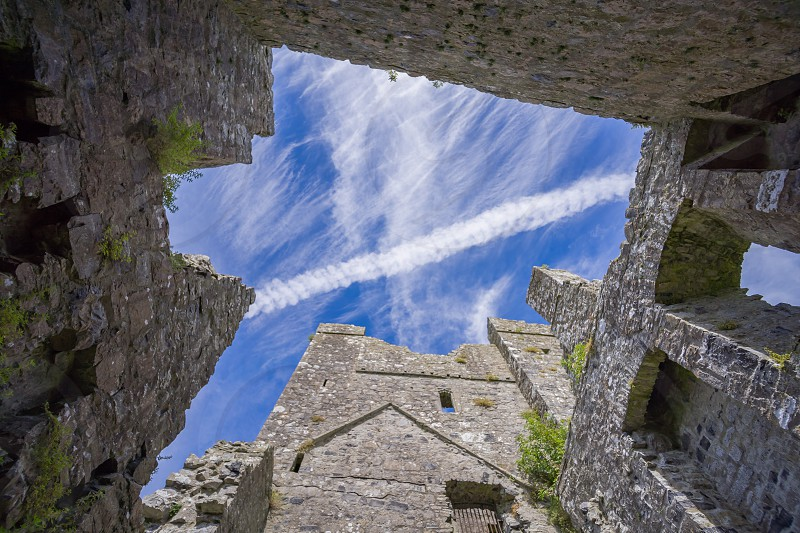A contrail in a blue sky as viewed through the ruins of an old monastery in Ireland. photo