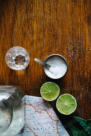 halved limes with an empty shot glass and salt on a wood table photo