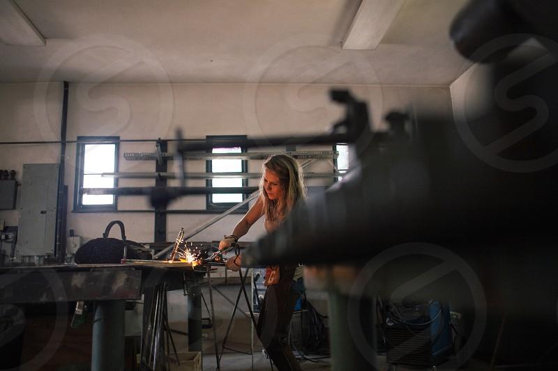 woman in grey tank top welding metal photo