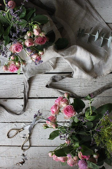 Arranging tea roses on vintage table with linen apron. photo