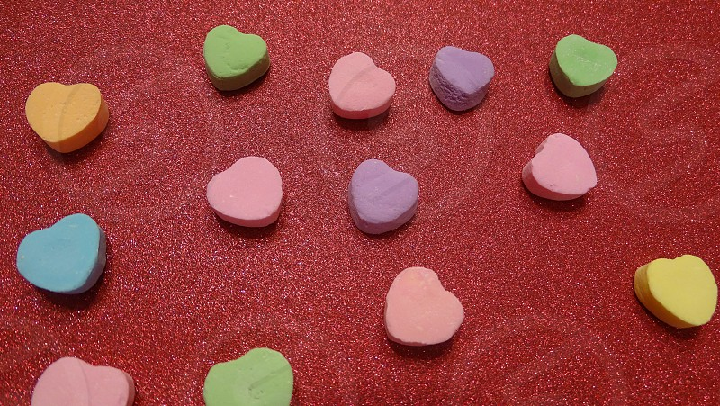 Colorful love hearts on red glitter background. Valentine's day decorating idea. photo