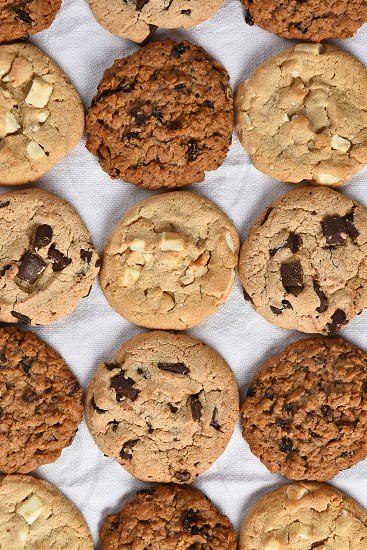 A group of assorted cookies. Chocolate chip oatmeal raisin white chocolate fill the frame. photo