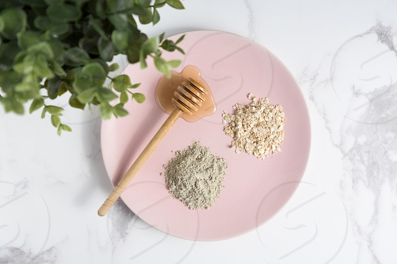 Flat lay of natural beauty ingredients including honey oats and benzonite clay on pink plate on marble background. photo