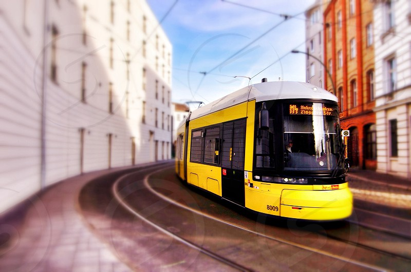 yellow train running on winding railroad inline of buildings photo