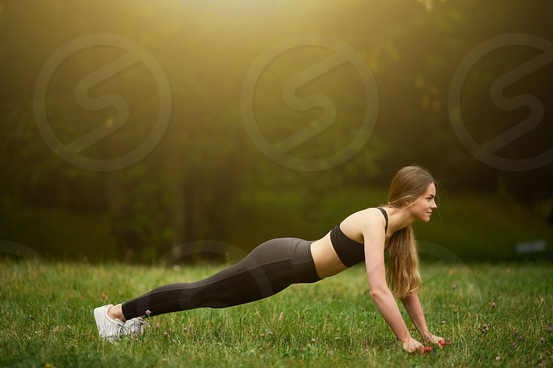 Pretty fit girl doing push ups on the park background photo