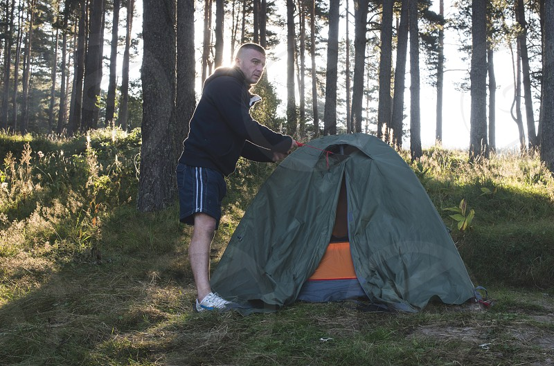 Man fix tent in the forest. Sunshine photo