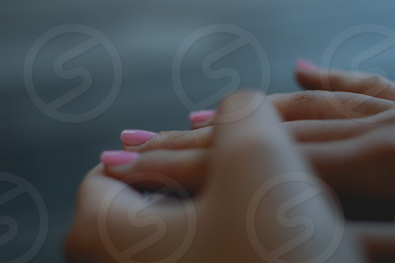 person's hand with pink nail polish photo