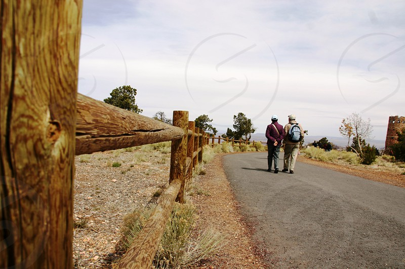 2 people walking on gray rolled asphalt road  beside brown wooden fence under white cloudy blue sky photo
