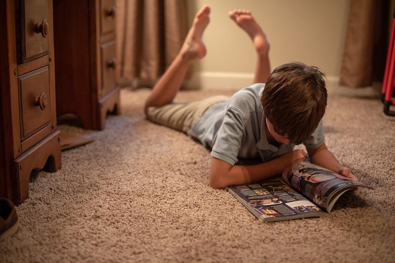 Boy or tween laying on floor indoors reading book photo