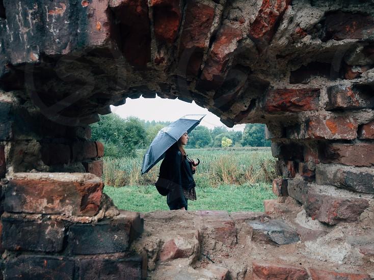 woman with black umbrella and brick wall photo