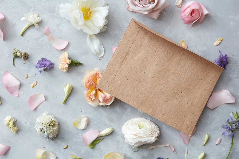 Paper blank and flowers on stone background. Mockup with flowers. Flat lay photo