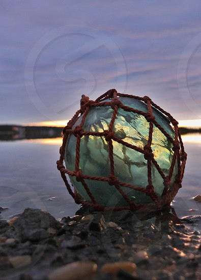 gray round stone wrapped in net photo