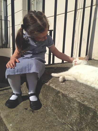 Schoolgirlsitting  downstreetstairsstrokingcatafter school photo
