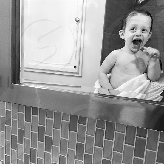 baby in grayscale photo white cleaning teeth photo