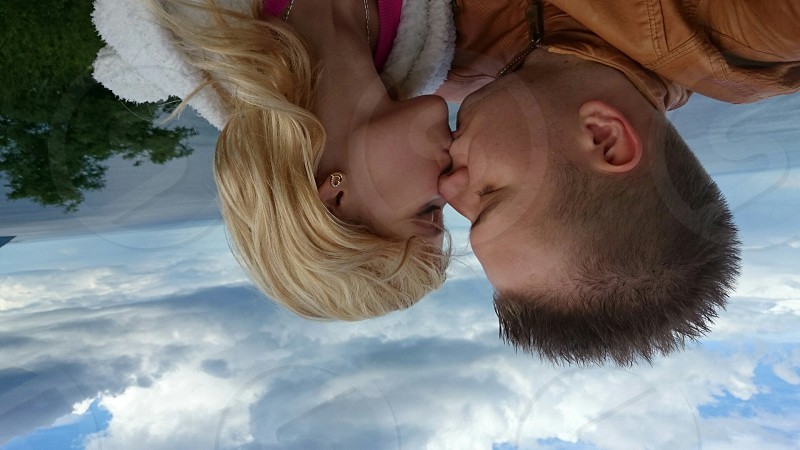 upside down photography of man and woman kissing each other during daytime photo
