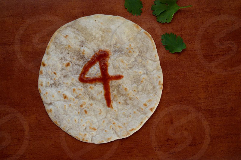 A closed top number 4 on a toasted tortilla on table top with cilantro photo