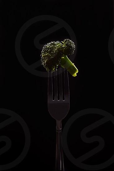 Broccoli on fork isolated on black background photo