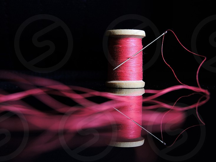brown wooden thread spool with pink thread photo